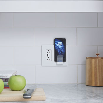 white wireless charger with phone on white kitchen back splash