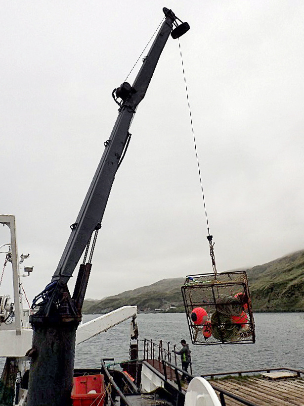 A crab pot being loaded onto our research boat.