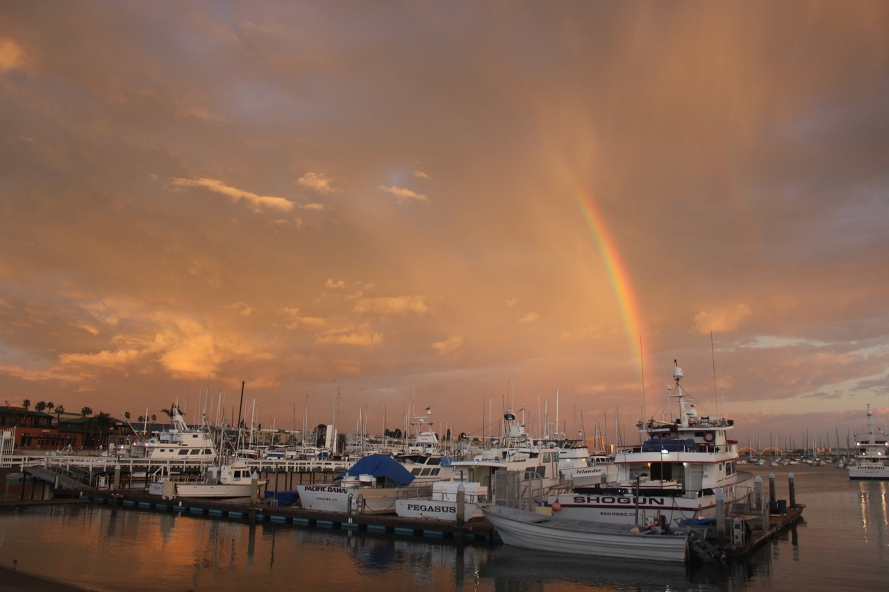 Dusk at the San Diego Harbor. A rainbow and golden sky is seen behind a row of boats docked against a small pier.
