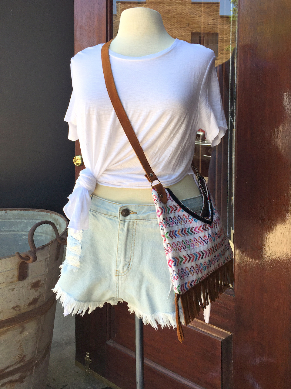 From Ambiance: white front-tie tee, $36.75; denim shorts, $39; handmade Guatemalan purse with fringe, $65