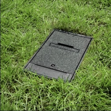 Black outdoor ground box installed in grass