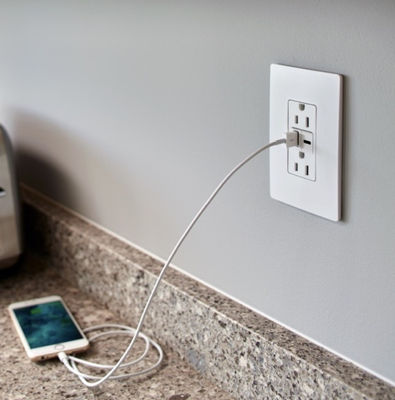 white outlet charging iphone on granite countertop