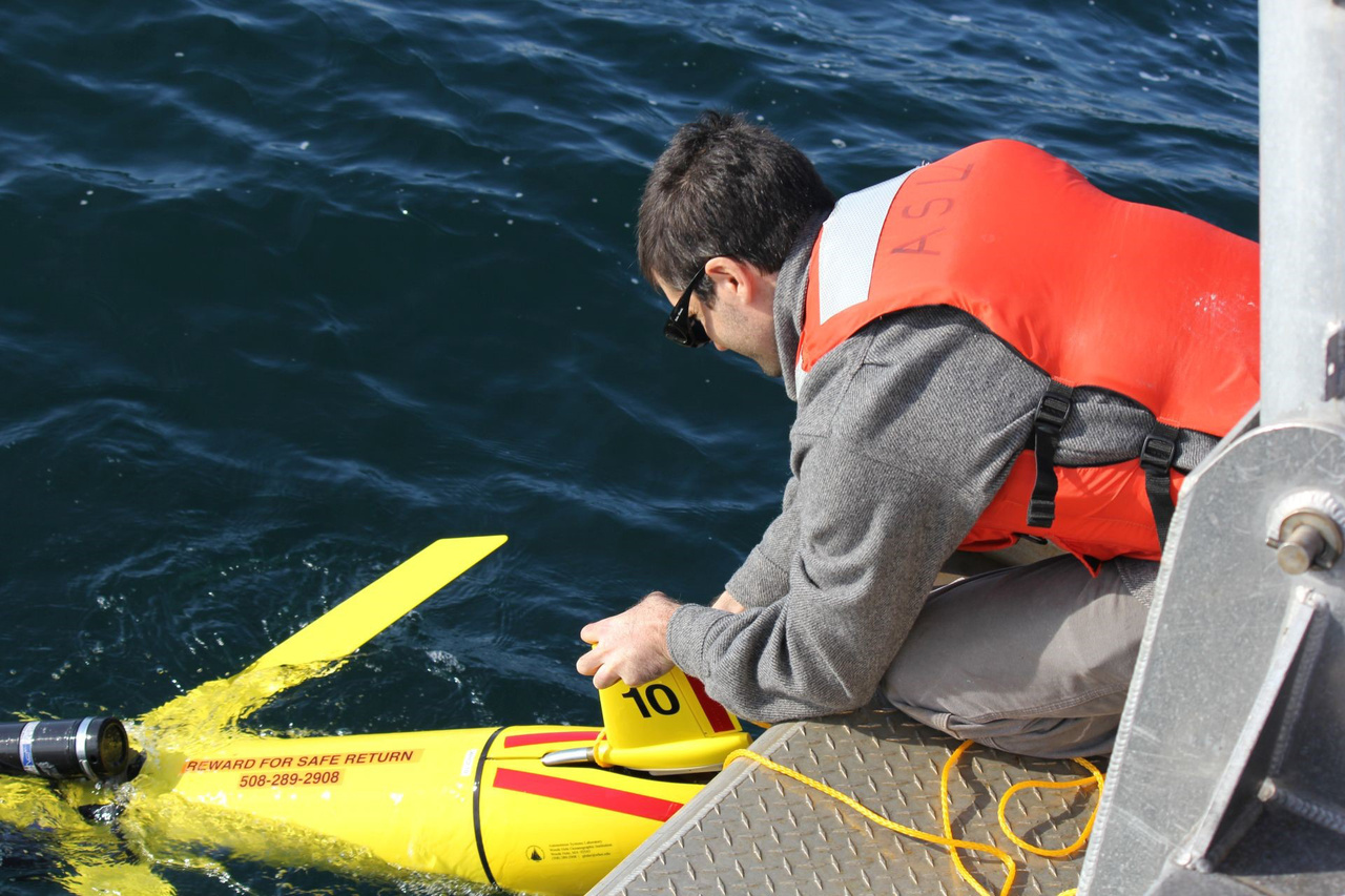 Man putting a a cylinder shaped glider with fins into the ocean from the back deck of a research vessel