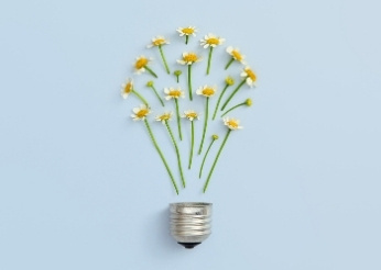 Lightbulb part with small flowers making a lightbulb shape against a light blue background