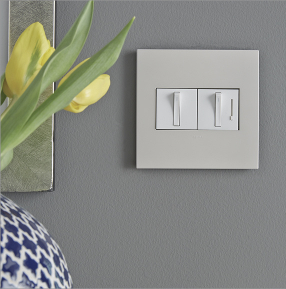 white adorne whisper switch and dimmer against gray wall