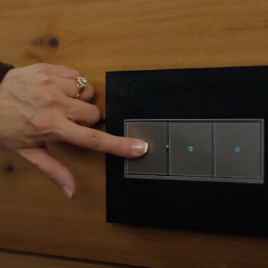 woman tapping magnesium switch and dimmer with black wall plate