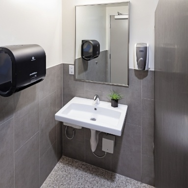 White porcelain sink with a mirror and soap dispenser mounted above and a paper towel dispenser mounted on the wall to the left