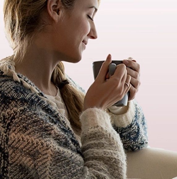 woman in warm sweater grabbing a warm mug