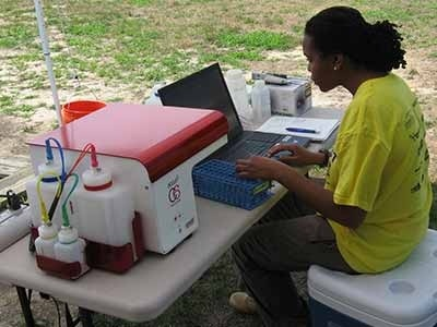 Scientist at computer doing field work.