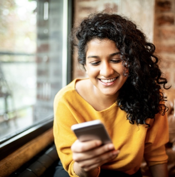 Woman in yellow shirt smiling while looking at her iPhone