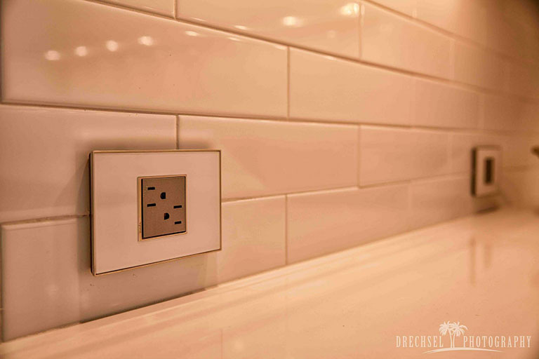 adorne tamper resistant outlet and mirror white wall plate on white tile