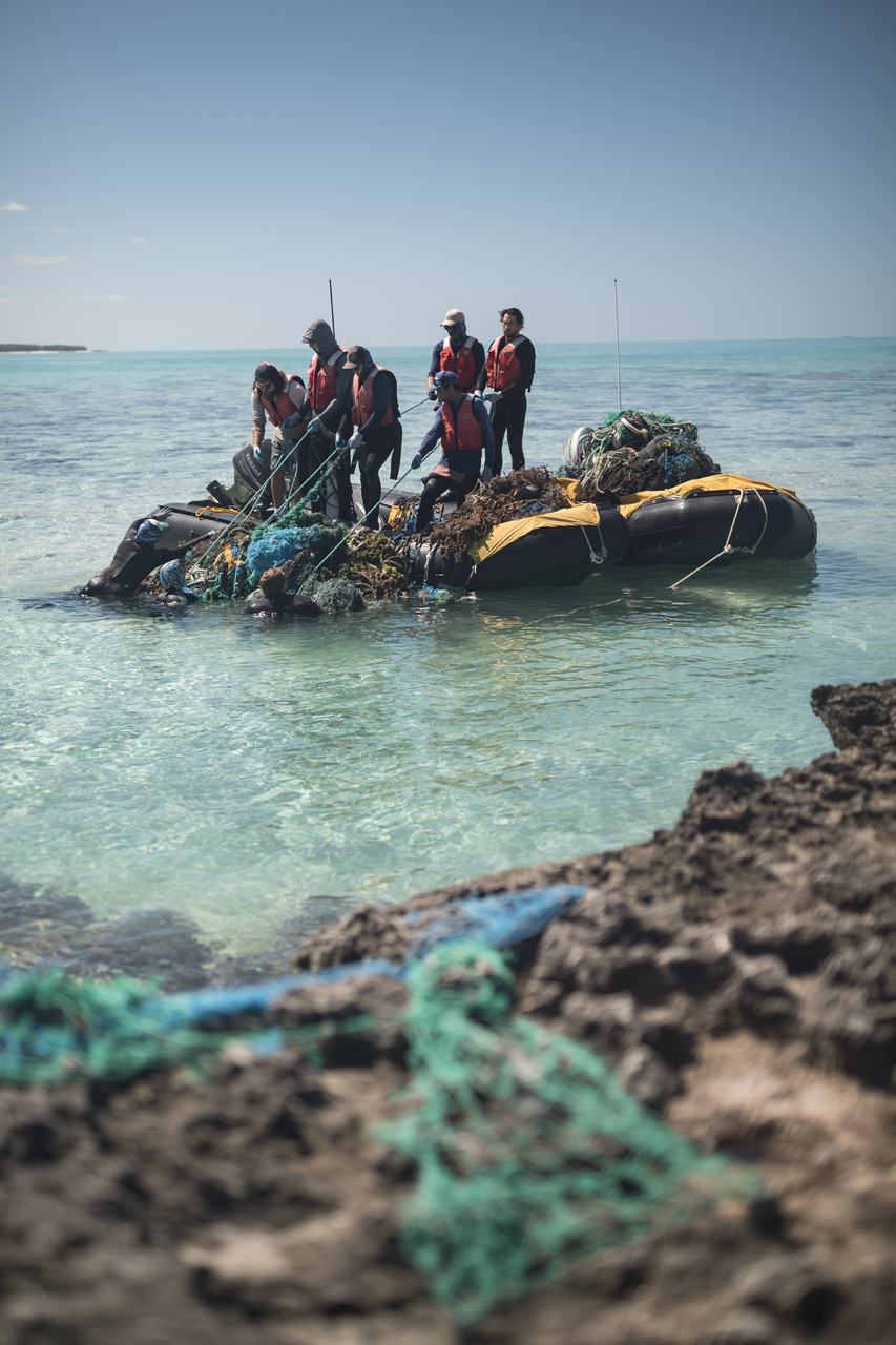 The team is about to bring the huge conglomorate net onto the small boat. Divers in the water tie the lines at the bottom of the nets to give everybody on the boat a tight grip. The small boats will be full! (Photo: NOAA Fisheries/Steven Gnam)