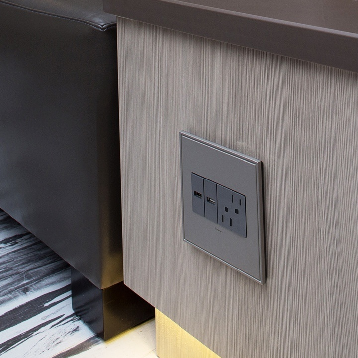 magnesium USB and standard adorne outlets built into gray table and seating area