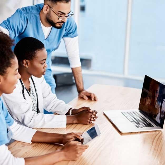 multiple people around a laptop