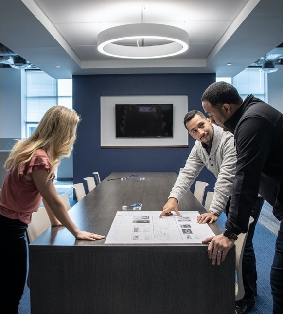 Two men and a woman reviewing floor plan designs at a conference table