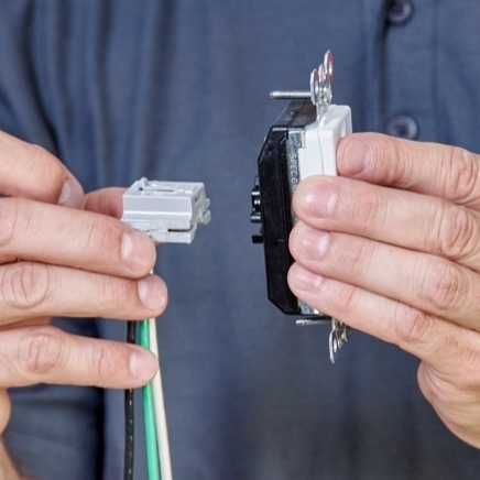 Hands demonstrating Plugtail wiring device