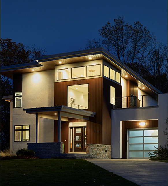 exterior of modern home at night with outdoor lights on