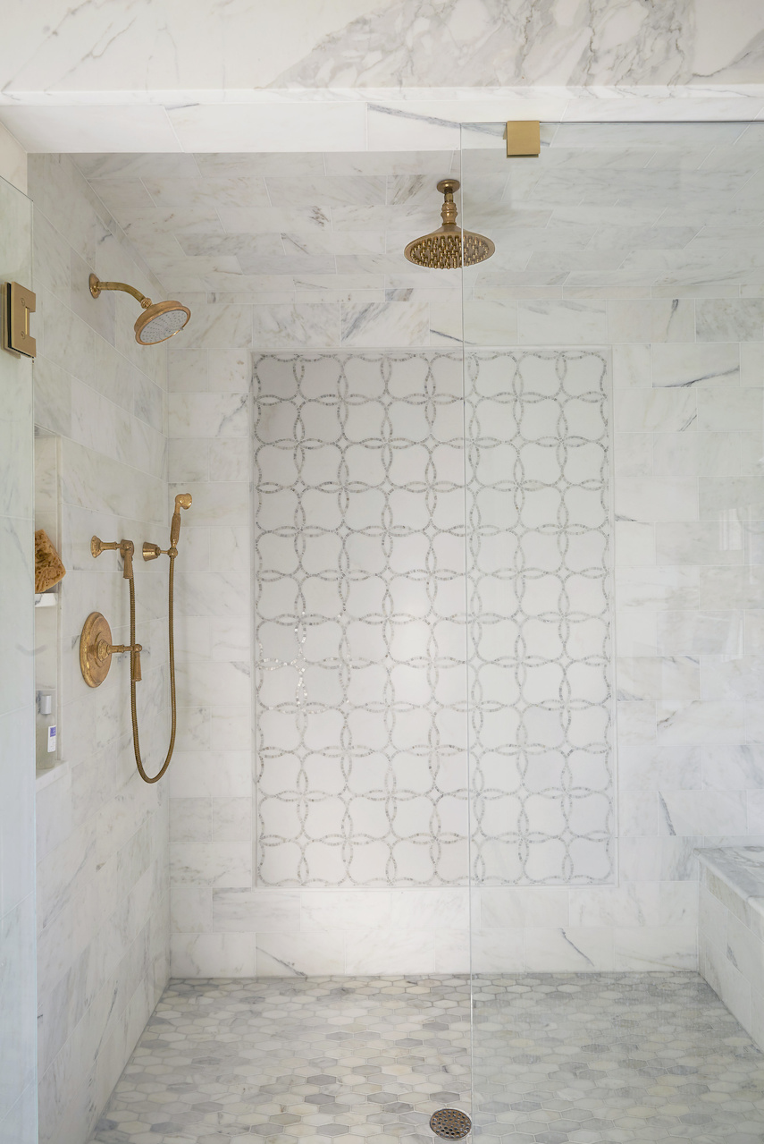 """Calcutta gold marble from Triton Stone, a wall mosaic from Fixtures & Finishes and unlacquered brass make for a stunning shower. """"I love the contrast that the gold of the unlacquered brass gives against the marble,"""" says Libby."""