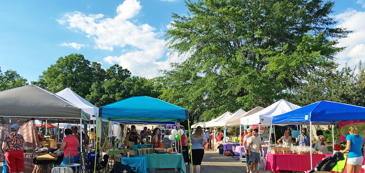 Colorful tents and shoppers enjoy a day under blue skies at the West Homewood Farmers Market.