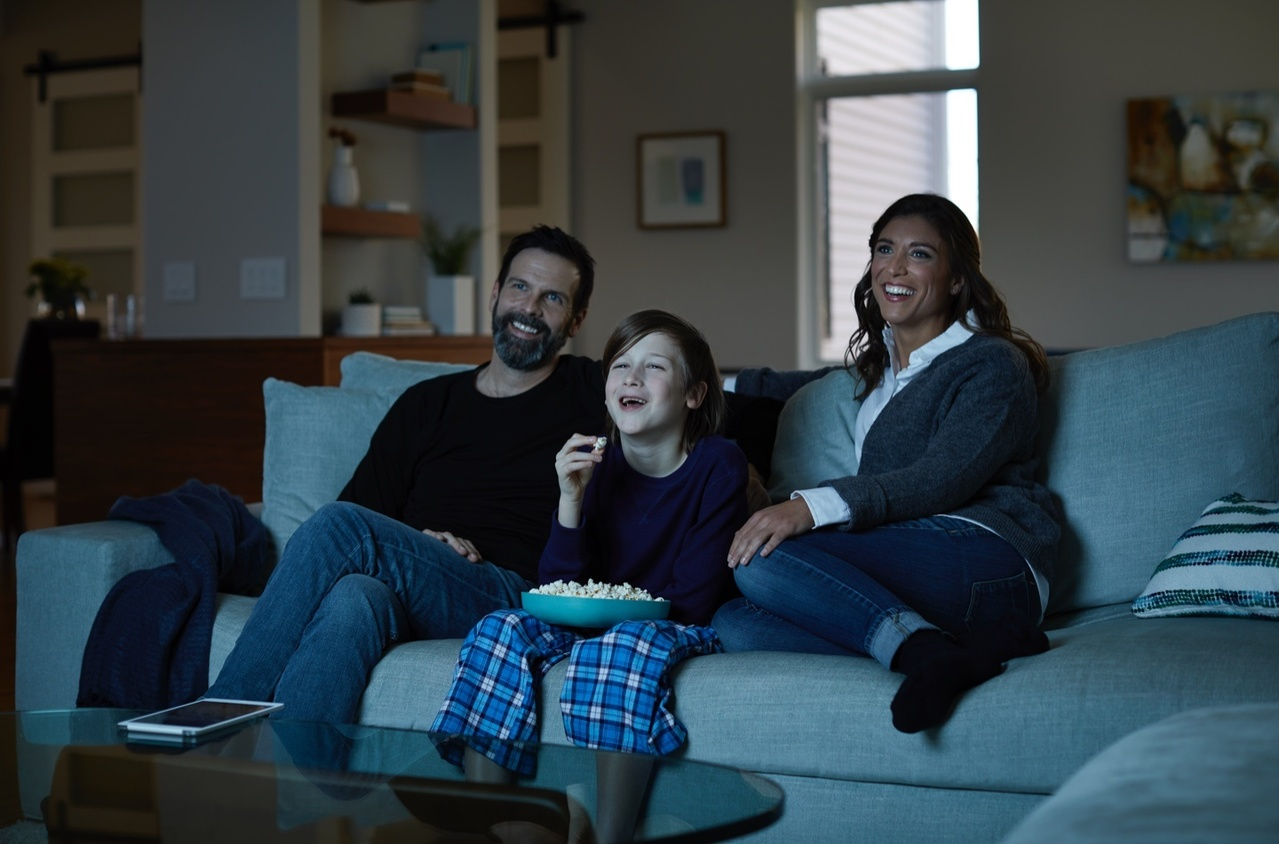 Parents and child sitting on couch laughing at tv