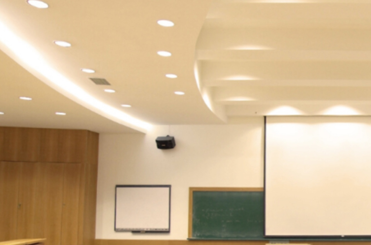Well-lit classroom with a projector screen and chalkboard at the front of the room