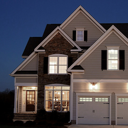 exterior of beige and brick home at night with all interior lights on