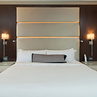 White hotel bed with gray headboard and mahogany walls