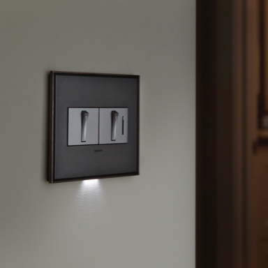 Light switch and dimmer with accent light below wall plate