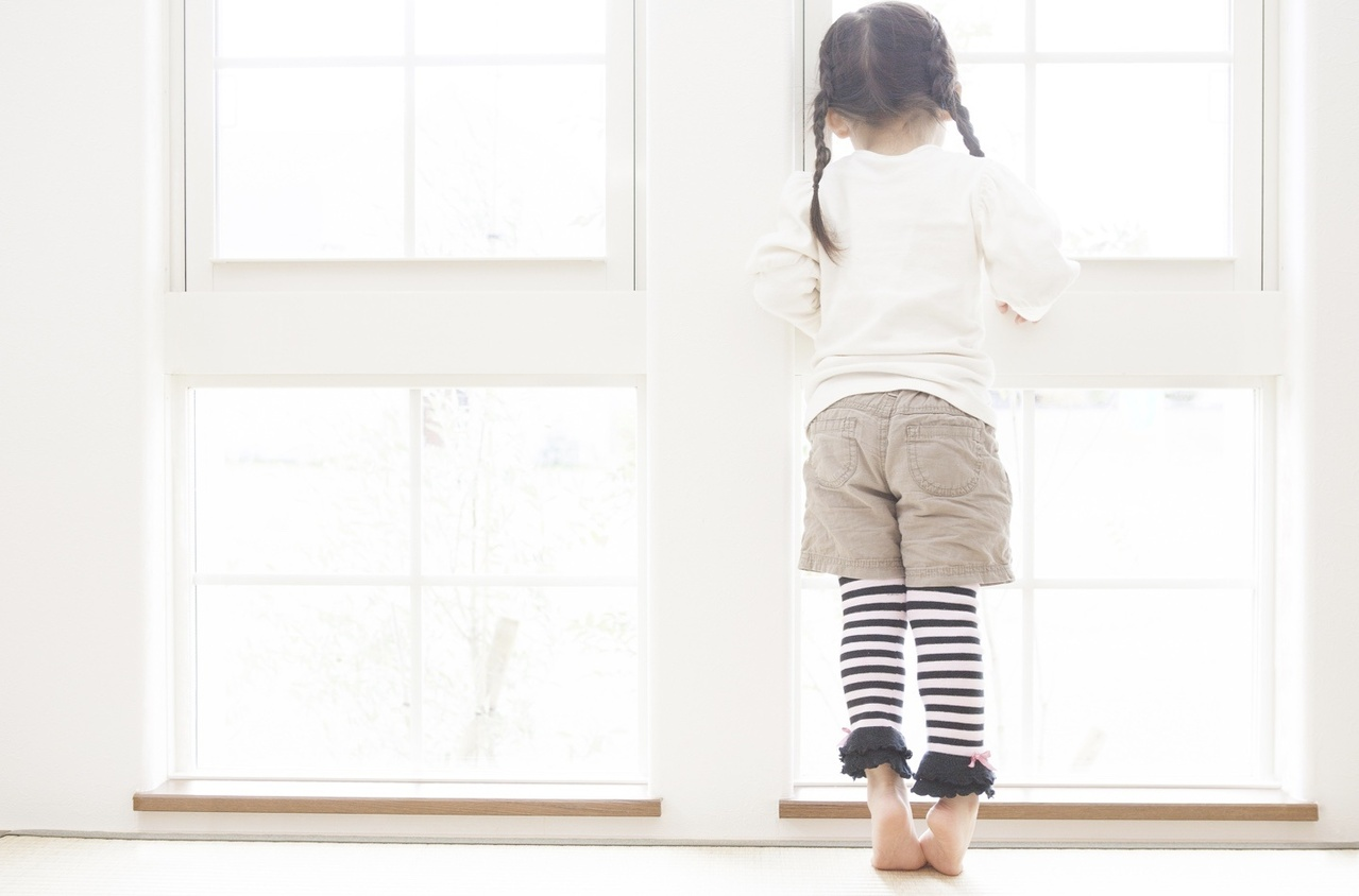 Small child standing at a window looking out