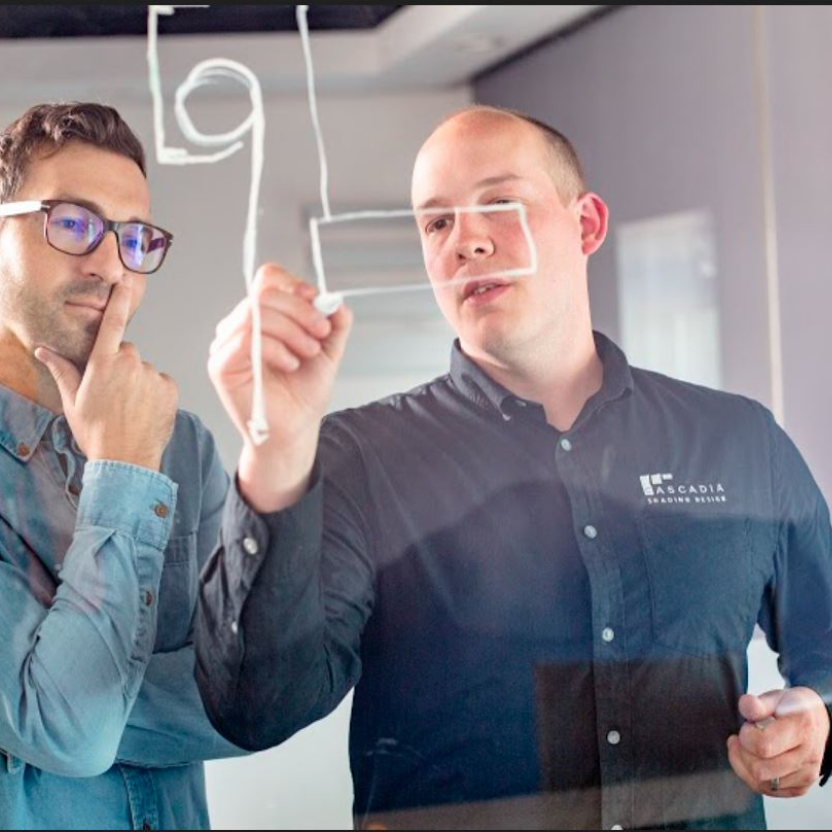 Two men working on a dry-erase board with a white marker
