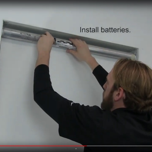 Person installing batteries on roller shade motor controller