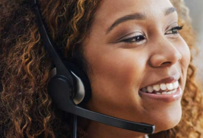 Woman speaking into headset with a customer.