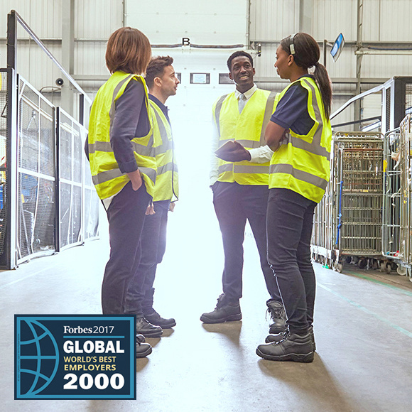 Four people in warehouse wearing reflective safety vests