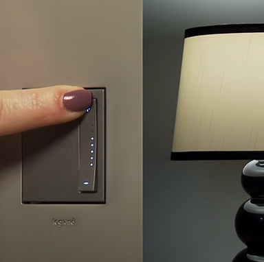 hand using Legrand's adorne Collection sofTap dimmer in magnesium