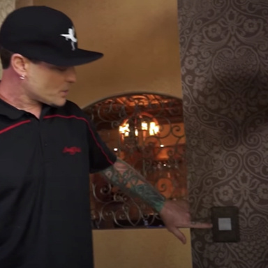 Vanilla ice pushing switch on patterned wall in mansion