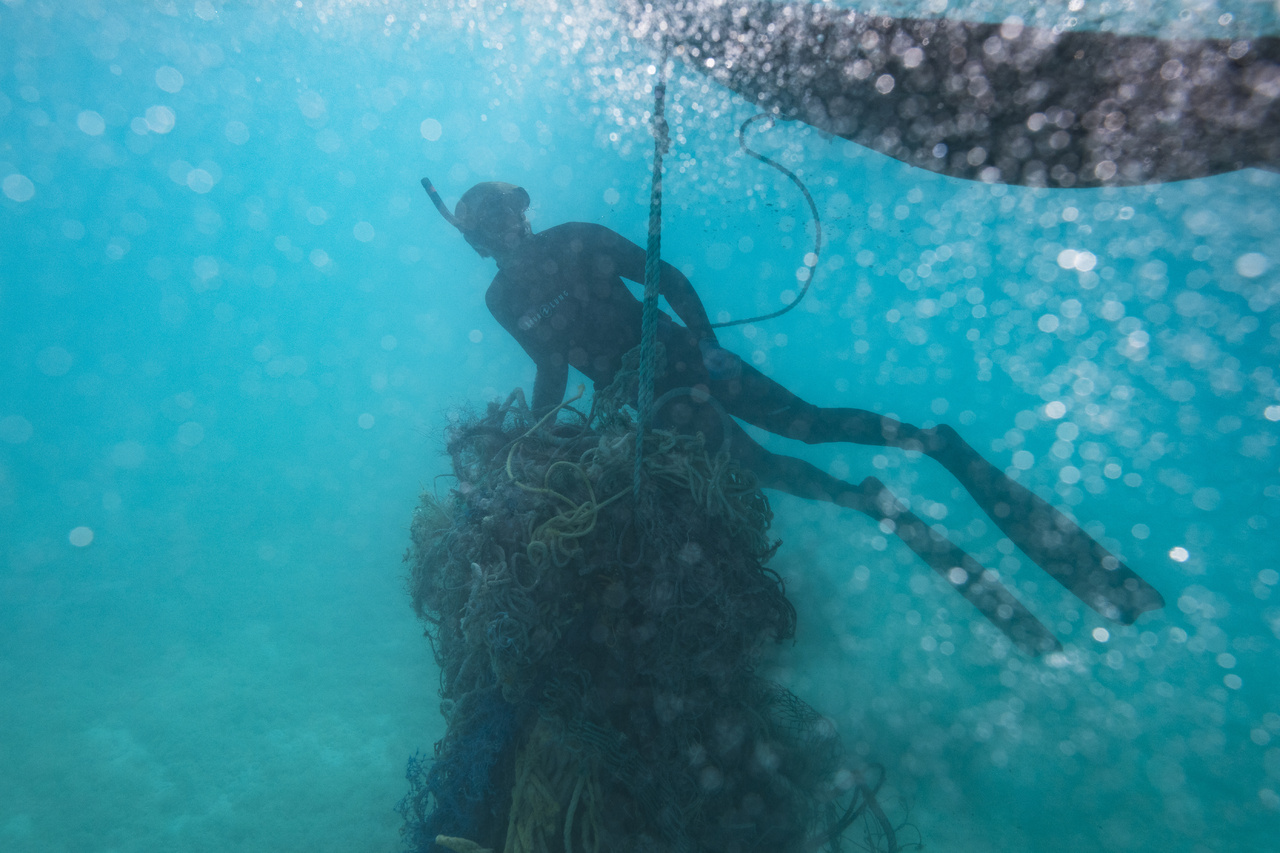 Marine debris diver Kevin O'Brien hauls derelict fishing nets back to the small boat for removal