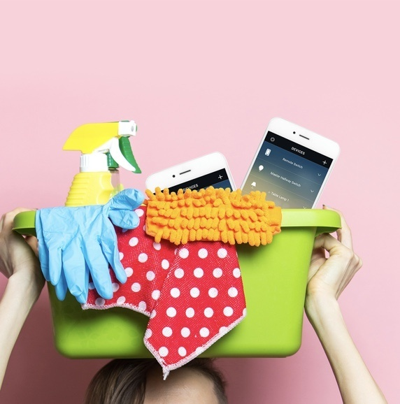 person holding green container filled with cleaning supplies and smart devices against pink wall
