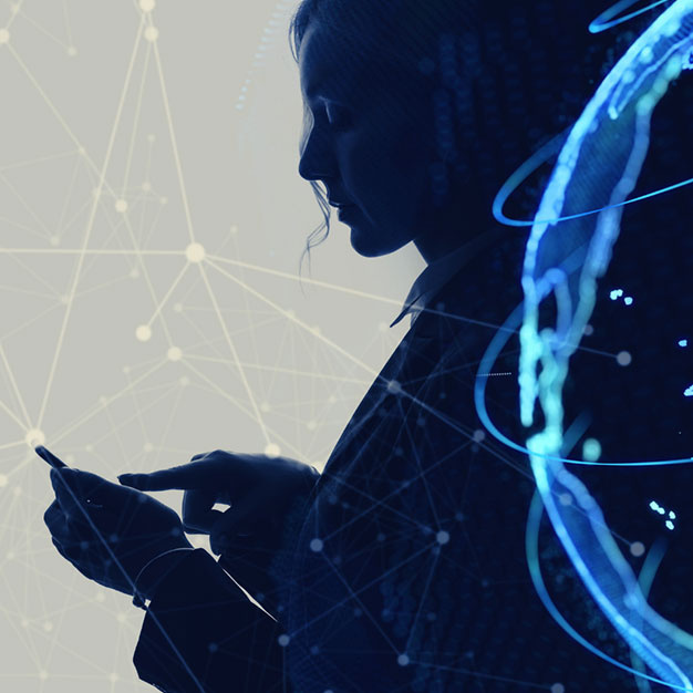 Silhouette of person using mobile phone with graphics of globe and interconnectivity