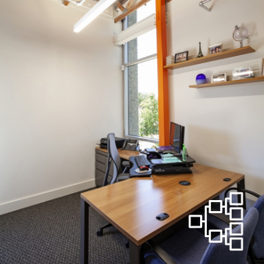 Small office with white walls and a large window containing an L-shaped desk, a rolling chair, two normal chairs, and a computer