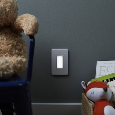 Nightlight installed in dark wall with children's toys on either side