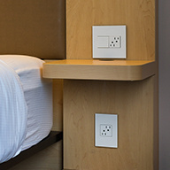 White outlet and switch next to hotel bed