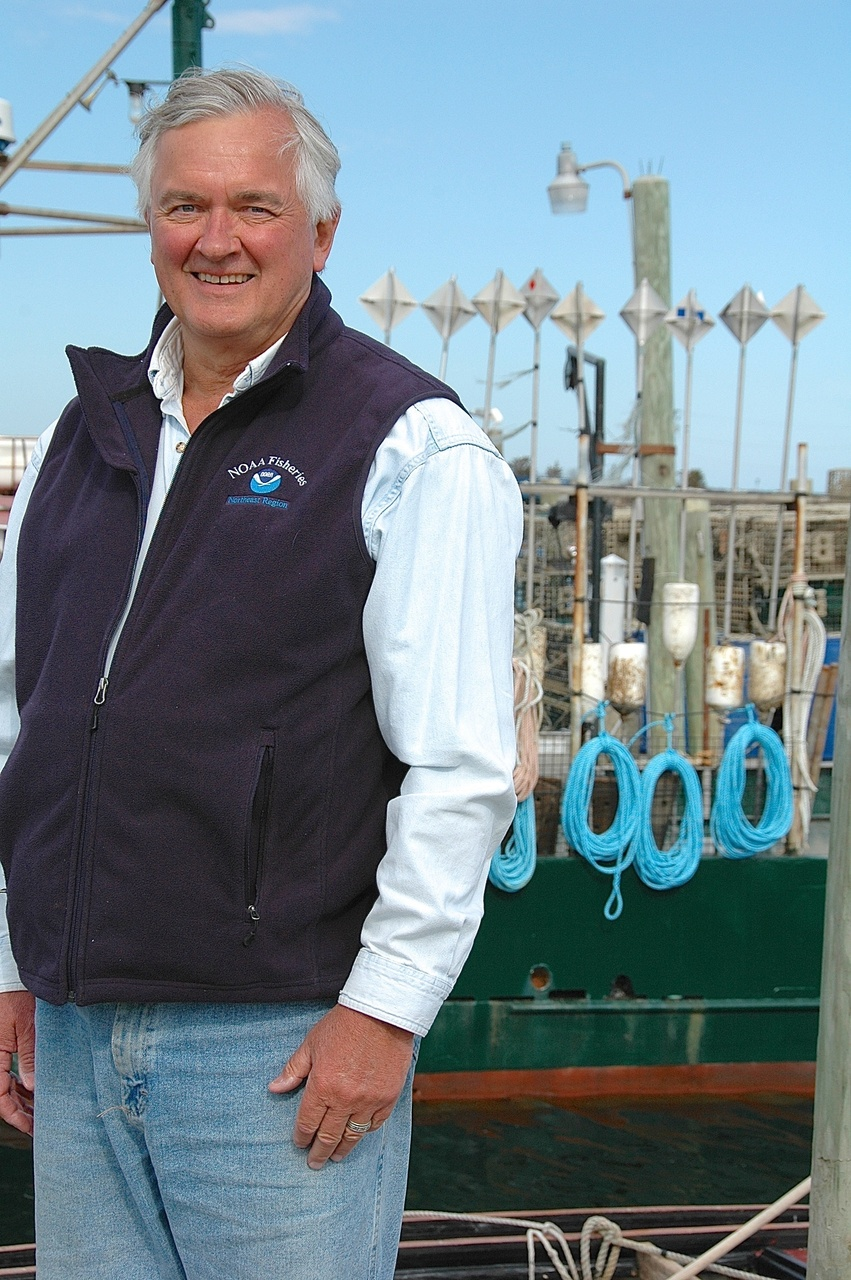 John Bullard stands in front of a fishing boars at the dock