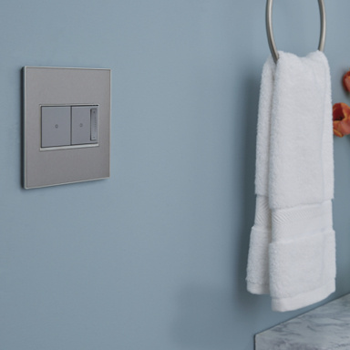 gray light switch and dimmer in blue bathroom next to white handle towel