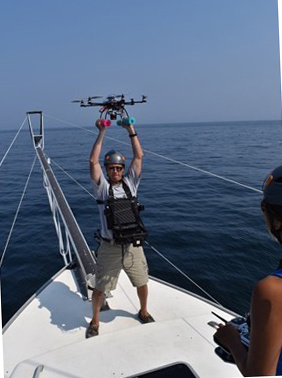 Mike Jech holds the drone high over his head just before a launch from the bow of a fishing vessel