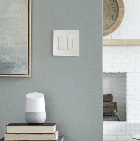 white radiant smart switch and dimmer on gray wall next to google home