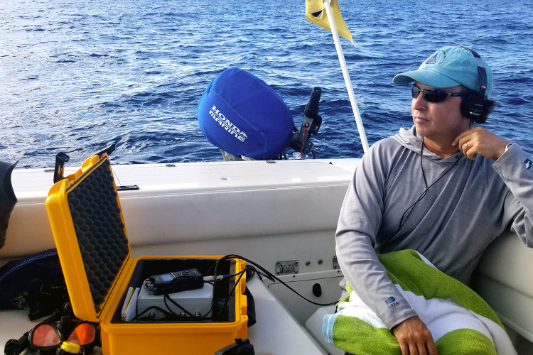 Researching sitting in a boat with headsets.