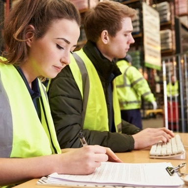 Man and Woman in yellow construction vests sitting at a table taking notes