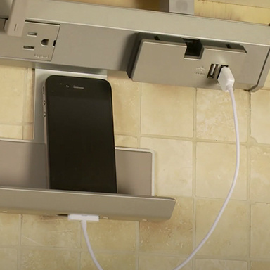 smartphone resting in cradle module of adorne Collection under cabinet lighting system