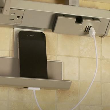smartphone resting in cradle module of adorne Collection under cabinet lighting system