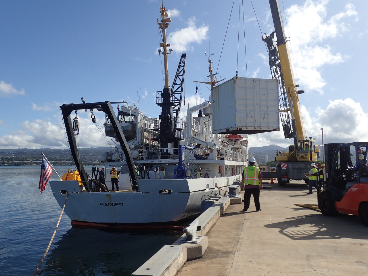 Loading day! Safety officals stand by as a large crane moves our mobile lab from the pier onto the <i>Rainier</i>. The scientists will use this for (air conditioned!) lab space to store and prep gear, as well as process samples from the field. <i>Photo: NOAA Fisheries/James Morioka. </i>